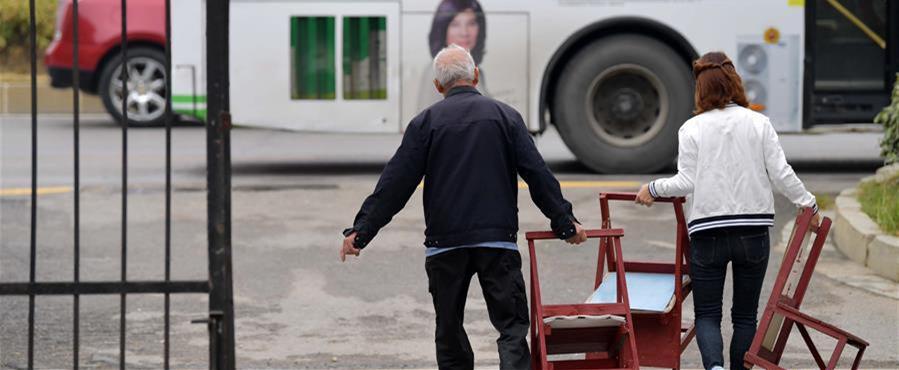 10月9日,在南昌市青山湖区湖坊镇肖坊村,李树子(左)和社区工作人员把刚做好的椅子搬到公交车站。