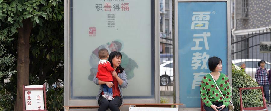 10月9日,在南昌市青山湖区顺外路口的公交车站,市民坐在爱心椅上候车。