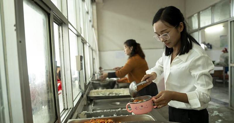 方荣在罗田县希望小学食堂给学生打饭。