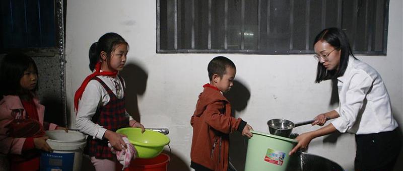 夜晚,方荣给罗田县希望小学住校学生打水洗漱。