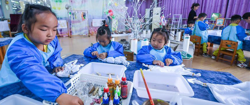 """10月23日,孩子们在老师的指导下将棉布用橡皮筋进行绑扎,准备用来扎染。今年以来,浙江省长兴县夹浦镇中心幼儿园依托当地传统布艺文化基础开设""""七彩课堂"""",引进布艺、扎染等传统工艺课程,让孩子们感受民间工艺的魅力。"""