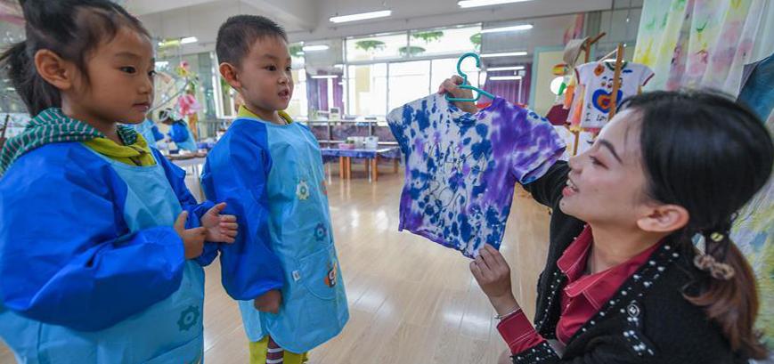 老师给孩子们介绍扎染工艺的步骤。