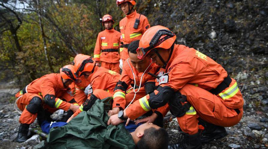 """10月27日,国家综合性消防救援队伍组建一周年主题采访团走进丽江市,跟随丽江市森林消防支队玉龙大队指战员来到他们靠前驻防守护的玉龙雪山景区,聚焦玉龙雪山的守护者。图为玉龙大队的指战员在玉龙雪山景区腹地进行山岳救援演练,消防员对""""意外坠崖游客""""进行救护。"""