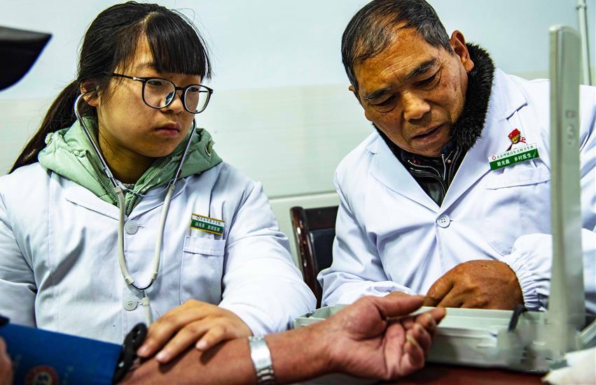 11月24日,大学生村医杨海燕(左)与村医裴光鑫一起为村民看病。
