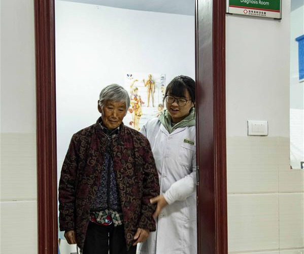 11月24日,大学生村医杨海燕与一名患者走出诊室。