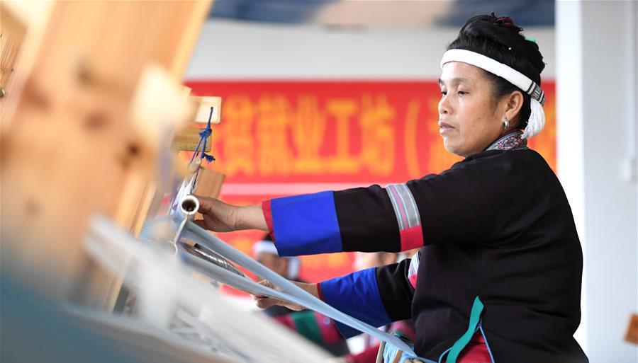 11月27日,在广西柳州市三江侗族自治县古宜镇南站社区易地扶贫搬迁安置小区,侗族妇女在扶贫就业工坊里织造侗锦。
