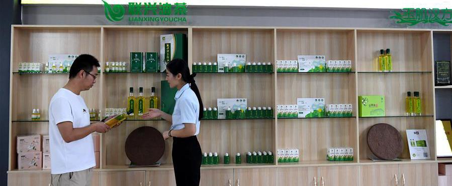 8月25日,在河南省光山县一家油茶加工企业展厅内,工作人员(右)向顾客介绍产品。