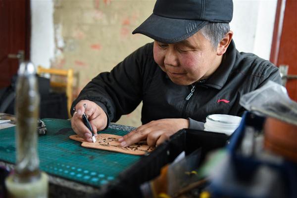 4月15日,在锡尼河镇的出租房内,米格木尔在皮制品上雕刻花纹。米格木尔家住内蒙古鄂温克族自治旗锡尼河镇孟根础鲁嘎查。年轻时因为一场意外,他的腿脚落下病症。2016年,因为缺失劳动能力,他成了建档立卡贫困户。 2016年下半年,女儿南吉乐玛需要到镇上的蒙古族幼儿园上学。为了孩子的学习,独自抚养女儿的米格木尔选择离开牧区来到镇上租房陪读。因为腿疾不便打工,租房生活支出也大,虽然看病不用花钱,但米格木尔的生活压力还是不小。 正当米格木尔犯难之际,2018年春天,当地就业部门推荐他去民族文化产业创业园参加皮雕手艺培训。米格木尔十分珍惜这次培训机会,坚持学习三个月后,他便能独自在家做产品,并达到公司售卖标准。这个手艺让他居家赚钱、陪读两不误,逐步实现稳定脱贫。 在鄂温克族自治旗,通过民族文化产业创业园培训手工艺技能成为当地扶贫的一大特色。在园区内,民族特色企业达到了192家,囊括23项非遗传承项目。至今,创业园已为全旗近300户建档立卡贫困户开展特色产业培训。 新华社记者 刘磊 摄