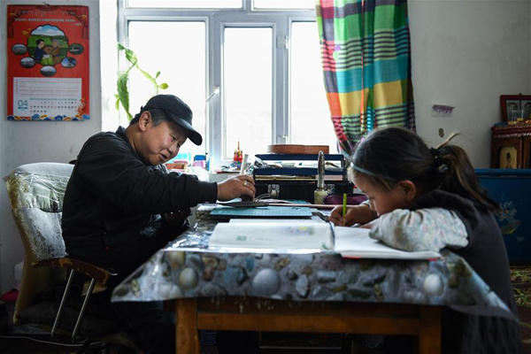 4月15日,在锡尼河镇的出租房内,米格木尔在进行皮雕,女儿南吉乐玛在温习功课。新华社记者 刘磊 摄