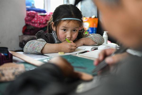 4月15日,在锡尼河镇的出租房内,女儿南吉乐玛写作业时看爸爸制作皮制品。新华社记者 刘磊 摄