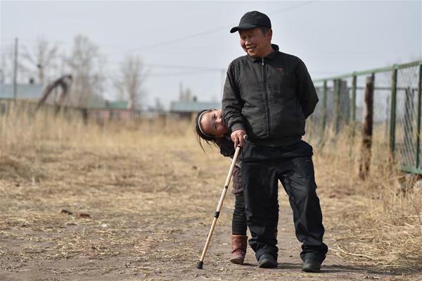 4月15日,在锡尼河镇的出租房外,米格木尔(前)和女儿南吉乐玛一起玩耍。新华社记者 刘磊 摄