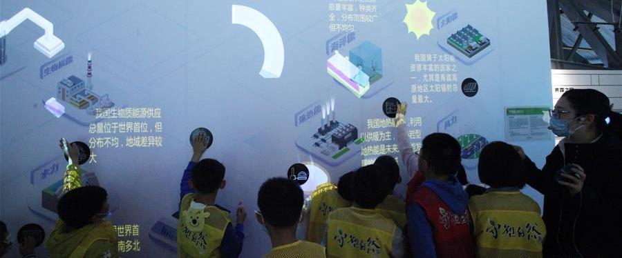 """11月1日,孩子们在南京科技馆参与""""中国能源概况""""科普项目的互动。 当日,《南京市生活垃圾管理条例》正式实施。南京科技馆结合自身科普资源,组织来馆参观的孩子们观看""""能源与环保""""展区,为他们讲解垃圾分类知识,让孩子们在互动中增强环保意识,从小养成爱护环境的良好习惯。"""