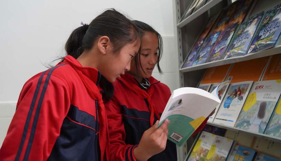 在四川省布拖县阿布泽鲁小学,海莫惹牛(右)和同学在新建的图书馆里阅读新书(6月23日摄)。