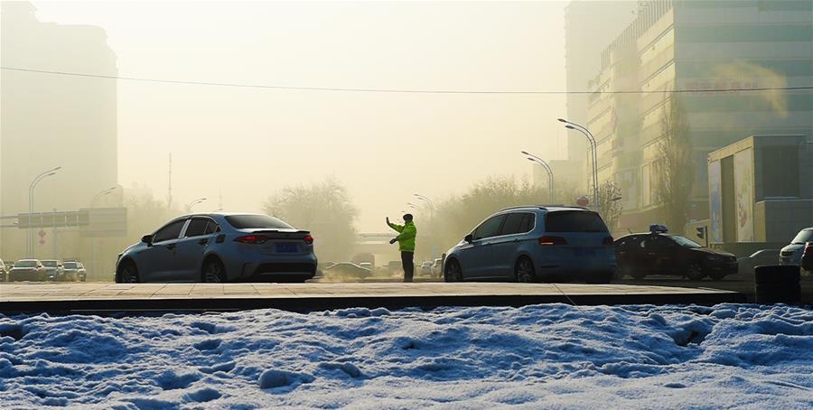 12月16日,在新疆乌鲁木齐,一名交警在路口指挥交通。近日,乌鲁木齐气温骤降,最低温度逼近零下20摄氏度。 近日,伴着寒潮到来,多地迎来入冬以来最寒冷天气,一些劳动者在凛冽寒风中依然坚守岗位。