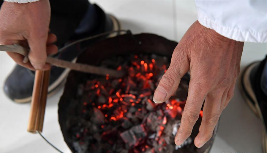 12月16日,在江西省宜春市宜丰县双木村,村医钟树新在村医务室烤火。近期由于气温骤降,当地山区白天的最高温度只有零下2摄氏度。 近日,伴着寒潮到来,多地迎来入冬以来最寒冷天气,一些劳动者在凛冽寒风中依然坚守岗位。