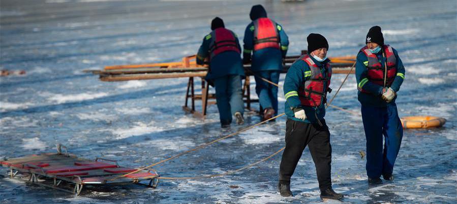 12月13日,工人在北京什刹海景区结冰的湖面上搭建围挡。 近日,伴着寒潮到来,多地迎来入冬以来最寒冷天气,一些劳动者在凛冽寒风中依然坚守岗位。