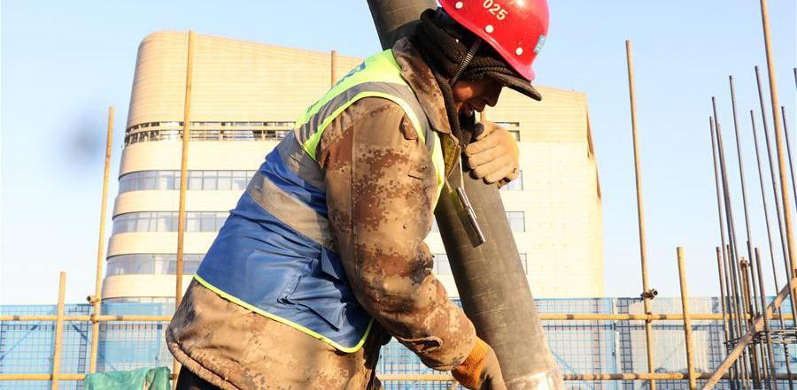 12月16日,在中建三局北京公司北京市大兴区一处项目工地,工人在浇筑水泥。 近日,伴着寒潮到来,多地迎来入冬以来最寒冷天气,一些劳动者在凛冽寒风中依然坚守岗位。